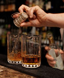 Bartender is pouring whisky in glass Stock Photography