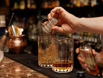 Bartender is pouring whisky in glass Royalty Free Stock Images