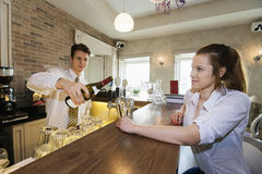 Bartender pouring wine for female customer at restaurant counter Stock Photos