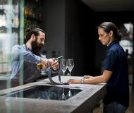 Bartender pouring a wine to the glass.  Royalty Free Stock Photos