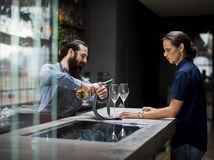 Bartender pouring a wine to the glass Royalty Free Stock Photos