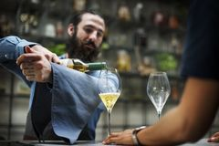 Bartender pouring a wine to the glass Royalty Free Stock Photography