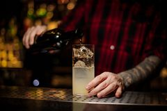 Bartender pourring a achohol from the bottle making a delicious royalty free stock images