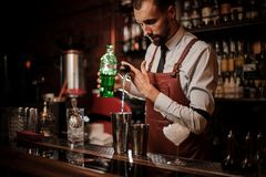 Bartender pourring an achohol from the measuring cup into a steel shaker. Bartender in the white shirt and brown leather apron pourring an achohol from the stock images