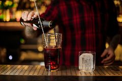 Bartender pourring an alcoholic drink into the measuring cup royalty free stock image