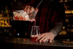 Bartender pourring a Sazerac cocktail from the glass measuring c royalty free stock images