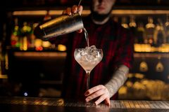 Bartender pourring a Sicilian Tonic achoholic drink from the cocktail steel shaker. To a glass on the bar counter stock image