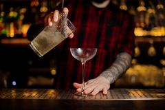 Bartender pourring a Twinkle achoholic drink from the measuring stock photo