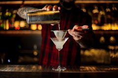 Bartender pourring a White Lady cocktail from the steel shaker. Through the sieve to a glass on the bar counter royalty free stock image