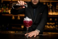 Bartender pours alcohol cocktail in glass with ice stock photography