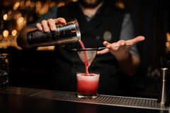 Bartender pours alcohol drink using shaker and sieve. Male bartender pours tasty alcohol drink using steel shaker and sieve on a bar counter royalty free stock images
