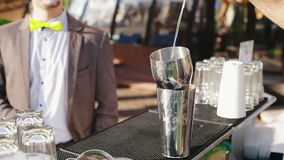 The bartender pours alcoholic ingredients for mixing. The bartender prepares alcoholic drinks outdoors stock footage