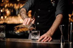 Bartender pours cocktail adding whiskey in glass royalty free stock photos