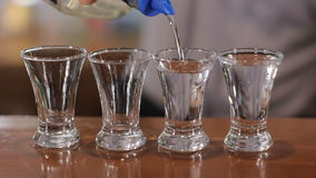 Bartender pours four shots of alcohol. Close up