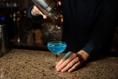 Bartender pours the last drops of the alcoholic cocktail Blue Lagoon from the shaker stock photography
