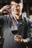 Bartender pours red wine in glass from big transparent vessel. Bartender in work uniform pours red wine in glass from decanter and stands in spacious cellar with Stock Photo