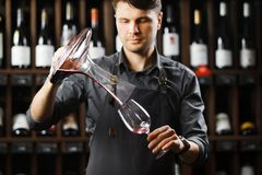 Bartender pours red wine in glass from big transparent vessel. Bartender in work uniform pours red wine in glass from decanter and stands in spacious cellar with Royalty Free Stock Photography
