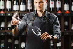 Bartender pours red wine in glass from big transparent vessel. Bartender in work uniform pours red wine in glass from decanter and stands in spacious cellar with Stock Photography