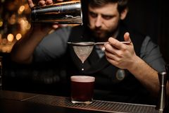 Bartender preparing alcohol drink with the shaker and sieve. Brutal male bartender with beard preparing red alcohol drink with the steel shaker and sieve at the stock photos
