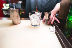 Bartender preparing a cocktail. Glass with ice on the bar. Night life royalty free stock photos