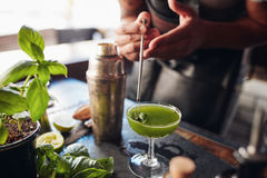 Bartender preparing fresh basil smash cocktail. Close up shot of barman hands garnishing fresh basil smash cocktail at the counter stock image