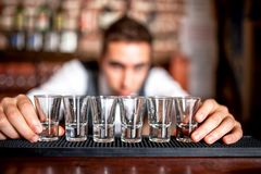 Bartender preparing and lining shot glasses for alcoholic drinks royalty free stock photos