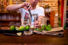 Bartender preparing mojito cocktail drink, with li royalty free stock photo