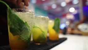 Bartender preparing refreshments in a nightclub. Bartender preparing orange refreshments wit mint ant lime in a nightclub stock video footage