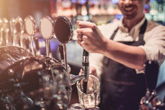 Bartender in pub. Cropped image of cheerful bartender on a bar counter is working and smiling Royalty Free Stock Photos