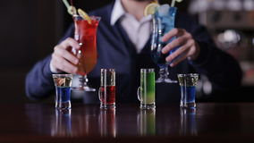 The bartender puts on the bar set of cocktails. stock footage