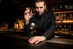 Bartender puts ice cube in alcohol cocktail stock image