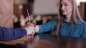 Bartender puts a straw in a glass with a cocktail and transmits it to the client stock footage