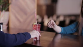 Bartender puts a straw in a glass with a cocktail and transmits it to the client stock video footage