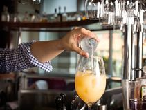 Bartender`s hand holding a botlle with alcohol drink and puring Royalty Free Stock Photos