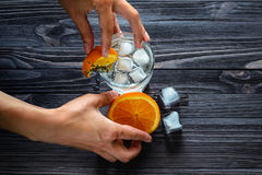 Bartender`s hands at work close-up. Preparation of a refreshing drink. Preparation of a refreshing drink with ice and citrus fruits on a dark wooden table stock photography