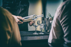 Bartender serving alcohol drinks Stock Photography