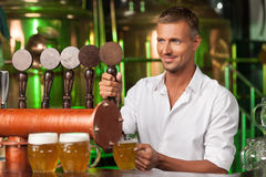 Bartender serving beer. Handsome bartender in white shirt servin Stock Photo