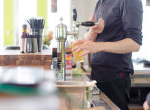 Bartender serving beer. A bartender pouring a beer to a customer at a bar Royalty Free Stock Photo