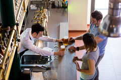 Bartender serving beer to couple Stock Photography