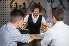 Bartender serving beer to customers. At bar counter in bar Royalty Free Stock Images