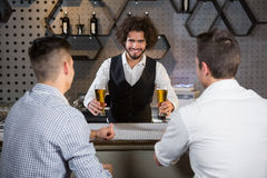Bartender serving beer to customers. At bar counter in bar Stock Images
