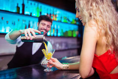 Bartender serving cocktail to young woman at counter Royalty Free Stock Images