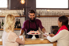 Bartender serving coffee to customers. In the bar Royalty Free Stock Photography