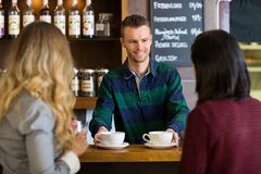 Bartender Serving Coffee To Female Friends At Cafe. Young bartender serving coffee to female friends at cafe Stock Photography