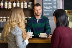 Bartender Serving Coffee To Women At Counter In Stock Image