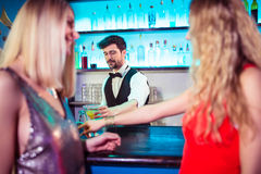 Bartender serving drinks to female customers. At nightclub Royalty Free Stock Photography