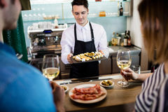 Bartender serving food to customer at counter Stock Photo