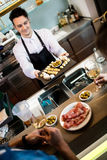 Bartender serving food to customers at counter. Handsome bartender serving food to customers at counter in restaurant Stock Photos