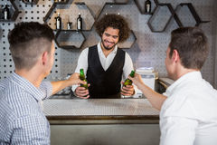 Bartender serving glass of beer to customers. At bar counter in bar Stock Photography