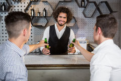 Bartender serving glass of beer to customers. At bar counter in bar Royalty Free Stock Photography